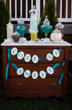 Candy favor bar, teal colored candies in apothecary jars, antique chest candy bar display and teal handmade love is sweet garland.