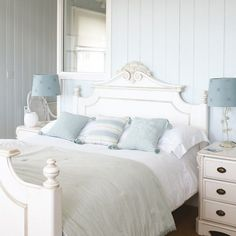 White-painted furniture looks great against pale blue walls in this fresh and light country-style bedroom.