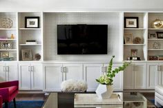 Gray and white patterned wallpaper lines the back of this built-in entertainment center to add interest and elevate the simple white shelving unit. Carefully styled shelves showcase family photos and pretty coffee table books.