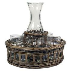 Woven willow basket holding six drinking glasses and a coordinating carafe.   Product: 1 Glass carafe, 6 glasses, and 1 willow basket   Construction Material: Glass and wood   Color: Clear and natural  Features:  Decorative Functional    Dimensions: 11.02 H x 3.74 W x 11.81 D (overall)   Cleaning and Care: Glasses are dishwasher safe, carafe must be hand washed and the basket can be wiped with a damp cloth