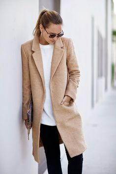 Simple and stylish. White tee, camel coat, and black pants.