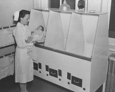 A 1940s nurse holds a baby in front of an incubator unit at the Kensington…