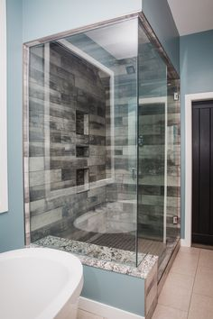 Amazing bathroom Walk in Shower featuring York wood manor tile color birch tree from Dal tile granite bench with full enclosed glass walls home by Neuhaven Developments flooring by Floorright Interiors