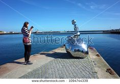 "Helsingor, Denmark - 06 May, 2018: Tourist photographing sculpture ""Han"" of naked young man siting on stone gazing at sea by Elmgrin and Dragset, Sculpture repeats pose of Mermaid in Copenhagen"