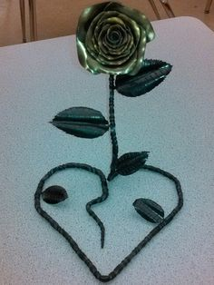"""The result of venting my frustrations this week. 3/8"""" round stock drawn down to 1/4"""" then added 3/4 twists.  Next was forming the rose, shaping the heart and finally adding the leafs.  I heated the rose and then hit it with a brass brush for a different look.  All and all about 4 days of work."""