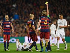 "The referee shows the yellow card to Barcelona's Argentinian defender Javier Mascherano (C) during the Spanish league ""Clasico"" football match FC Barcelona vs Real Madrid CF at the Camp Nou stadium in Barcelona on April 2, 2016."