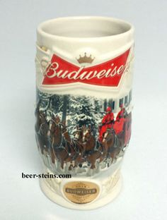 "1080411 - 2014 "" Holiday Lane "" Holiday stein. This 7"" stein was made in China. Features the Team & Wagon as it comes down a snow covered lane near a house. With Budweiser's classic red Bowtie and gold Crown at top, a raised A&Eagle ® , in white, on both sides of the center illustration and an oval, in gold, with 2014 Budweiser Holiday stein, below, may this classic holiday stein inspire you to find the road that leads to a place called home. http://www.beer-steins.com/budsteins/budxmas.html"