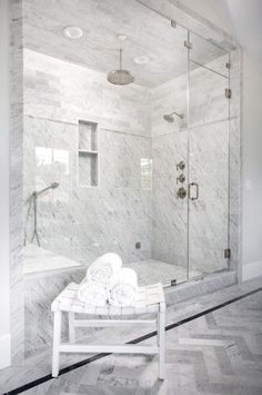 A white leather basketweave bench sits on gray herringbone floor tiles in front of a spacious seamless glass walk in shower finished with a polished nickel circular rain shower head hung from a marble tiled ceiling over a marble floor framed by mixed marble wall tiles framing a tiled niche as the shower is completed with a marble tiled bench and a two polished nickel shower heads.