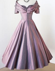 1950's lavender iridescent party dress in the Classic Silhouette with a fitted bodice, a dramatic wrap and gathered shelf-bust shawl collar, beaded and rhinestone-encrusted sweetheart bust, inside belt, and a full skirt. No maker label.