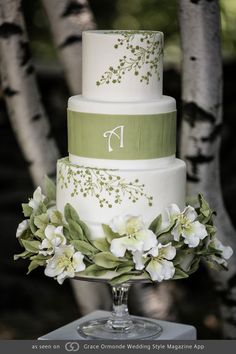 Cake finished in white Swiss fondant featuring piped green trailing vines, textured fondant band with monogram detail, sugar flowers and leaves.