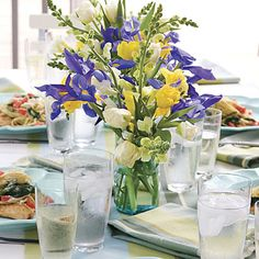 Purple irises, yellow tulips, and white roses in a glass vase make a classic statement for a spring centerpiece.