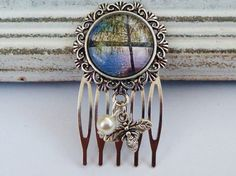 This exclusive small hair comb is a beautiful gift idea. It is made of silver metal and a solid frame with filigree border. The glass cabochon is handmade and shows a beautiful scene with tree on a lake.   Below the setting I have a bee charm and a real shell core pearl attached.     The hair comb has the dimensions 5.2 L x 3 W cm.     Further matching jewelry or hair jewelry may at any time be made.     Each piece of jewelry comes on a nostalgic card and in an organza bag to you; ideal for…