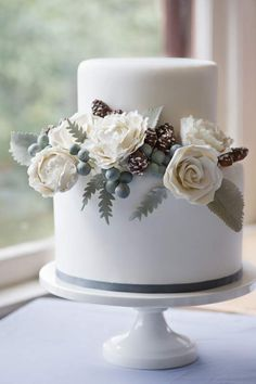 Beautiful silver white and pinecone wedding cake perfect for a winter white wedding by Erica OBrien Cake Design