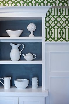 built in shelves w/ background color; high moldings with a strip of wallpaper