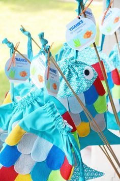 """Rainbow Fish / under the sea party: fish-shaped fabric drawstring bags with felt scales and eyes, tied onto a dowel rod with a printable fish tank tag """"Thanks for swimming by!"""""""