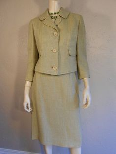 Circa: Late 1950s A lovely addition to the your Autumn Wardrobe, soft apple green almost a soft olive colour, in a tweed - wool blend two piece box suit. Large button front placket on the jacket, boxed style. Straight skirt. Lined jacket. Skirt has side zipper and button on the side. *Accessories not included but available separately * Label: Sam Silberstein Original Fabric: wool tweed, acetate lining Condition: Excellent Vintage Condition. * 2 small stains one on lapel, one on skirt…