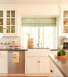 White cabinets, gray counters, casework around window.