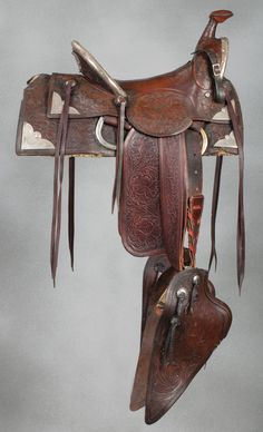 """Al Furstnow Hollywood Show Saddle circa 1920s, floral carved slick fork, high back saddle with gullet and cantle trimmed in silver and mounted with engraved sterling corner plates. Saddle is equipped with later 21"""" tapaderos, replaced fenders and has a 15"""" seat. A rare example of the ill-fated venture by the iconic Miles City, Montana maker to grab a piece of both the Hollywood cowboy and Rancheros Visitadores trail riding market in the late 1920s. Shows heavy use and evidence of both…"""