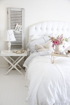 Cute, country elegance. Love the white-on-white (as I always do) and the small bed-side table with lamp. I also love the idea of using a window shutter to display photos. I think it's a good placement of the shutter as well.