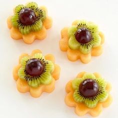 "How to Make fruit bites Flowers: 1. Use a 2""  cookie cutter to make shapes out of melon. 2. Use a 1 ½"" cutter to make shapes out of kiwifruit, and put a sliced red grape in the center. This cute snack idea is courtesy of www.parents.com"