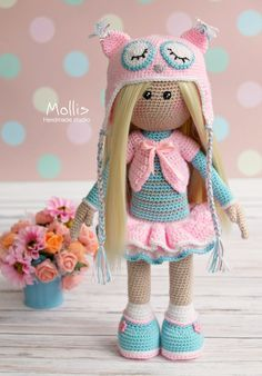 Crochet doll in pastel colours wearing an owl hat.