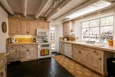 Rustic Kitchen with flush light, Raised panel, Woodhaven Plank Wood Ceiling, Limestone Tile, Inset cabinets, Exposed beam