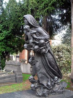 """The statue on the grave this grave has an entirely different name I am sure. This PHOTO was named """"Being taken to heaven?"""" By clspeace who has been a FLickr Member since 2005 Taken on March 10, 2007 Oggiaro, Milan, LM, IT Canon PowerShot A620"""
