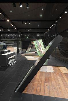Aus dem Boden ragende architektonische Zitate von Bodenpaneelen ragen in die dritte Dimension und heben das Thema Bodenbelag auf Augenhöhe.