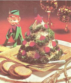 """Tuna fish molded into a cone and decorated like a Christmas tree. Wow. Is that the Elf on the Shelf in the background? We can't look long enough to decide. (He's everywhere!) From """"Treasury of Holiday Ideas"""" (Better Home and Garden, 1968)"""