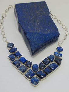 "Twenty hand-cabachon Lapis Lazuli gemstones adorn this artisan double-strand necklace, bezel-set in 925-hallmarked sterling silver, with lobster claw clasp. Length: 15-20"". Longest center dimension: 2"