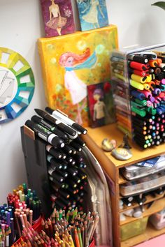 Plastic containers used to vertically stack markers and inking pens, cups used to hold colored pencils.