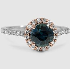 A premium teal round sapphire is surrounded by a halo of brilliant scalloped pavé diamonds in the Serenity Diamond Ring.