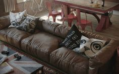 Sleek-Brown-Leather-Sofa-Design-and-Animals-Pillow-at-the-Living-Room-with-Union-Jack-Coffee-Table-on-Floral-Carpet-in-Den-Loft | Vintage Industrial Style