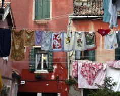 Photograph of laundry hanging out to dry in Venice, Italy, in a gorgeous, rose-colored piazza. The fabrics are flower-printed dish towels.