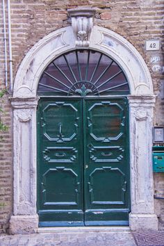 Green door with decorations and architrave in Senigallia, Marche Region, Italy