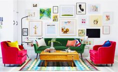 Oh Joy's studio living room with green and pink sofas and gallery wall of framed, colorful art.