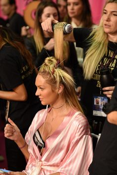 Candice Swanepoel multitasksbackstage at the 2015 Victoria's Secret Fashion Show.