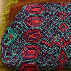 Aztec Beaded Clutch Use it as a clutch or for make-up, whatever you put into this adorable bag will stay put. Solid wood handles with a kissing lock securely fasten closed.  One side is a solid sheet of beadwork in bright fun colors. Sides are made up of 3 layers of material for long lasting use. There are some markings on the interior but very gently used. Bags Clutches & Wristlets
