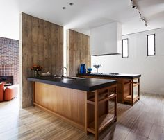 To delineate the living area from the kitchen, a split dark concrete panel forms a partition.