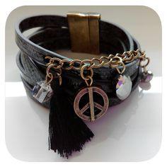 Pulsera triple de dos vueltas. Con abalorios simbolo de la paz, cristales y borla en color negro. Cierre de imán
