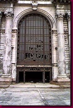 Michigan Central Railroad Station     Gateway to immigrants and visitors to Detroit for decades, Michigan Central Railroad Station saw millions of people pass through its doors. Now a massive ruin of eerie proportions it houses a single visitor.    Partially visible in the right door, a local wino has taken refuge from the misting rain with his bottle of wine.