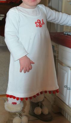 A $10 monogram and some red pom pom fringe make this white dress into the perfect Christmas (or Valentine's Day) outfit for a toddler girl.