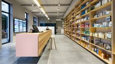 """Zware Jongens reimagined the traditional pharmacy to create this warm-toned space that includes a refreshment station and """"free-flowing"""" island counter"""