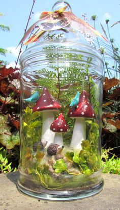 This woodland nature scene is nestled in a pretty glass jar.  The red mushroom, hedgehogs and bluebirds are made from polymer clay and hand painted.