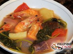 This is Sinigang Na Hipon (Shrimp in Sour Soup). Sinigang is a popular Filipino dish. It is a sour soup that uses tamarind as it's base flavor. See how to make it here: http://www.filipinochow.com/sinigang-na-hipon-shrimp-in-sour-soup/