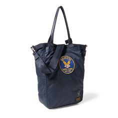 Pigment-coated nylon tote modeled after vintage Air Force helmet bags. Hand-applied military-inspired stamp at the bottom right corner.