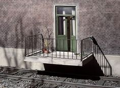 Frank Kunert. This is a photograph of a scale model.  Wow!! The detail on this model.  I love that the porch is in the way of the train!