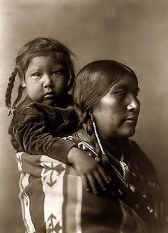 A Crow Indian Mother and Child~ Extraordinary photo of a Crow Indian Mother. It was made in 1908 by Edward S. Curtis.    The photo documents a Crow (Arapsoke) woman with a child secured on her back by a blanket.