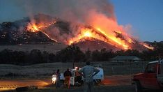 Farmers watch the flames rise above Jugiong, north of Canberra, January 2012
