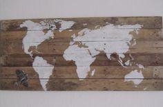 wereldkaart op een pallet geschilderd, met een vliegtuigje van Riviera Maison erop gemaakt.